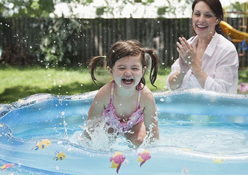 Little girl splashing in baby pool while mother watches