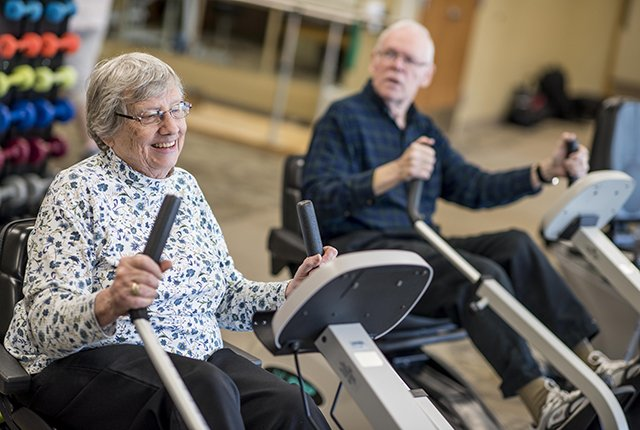 Two seniors exercising on recumbent bikes.