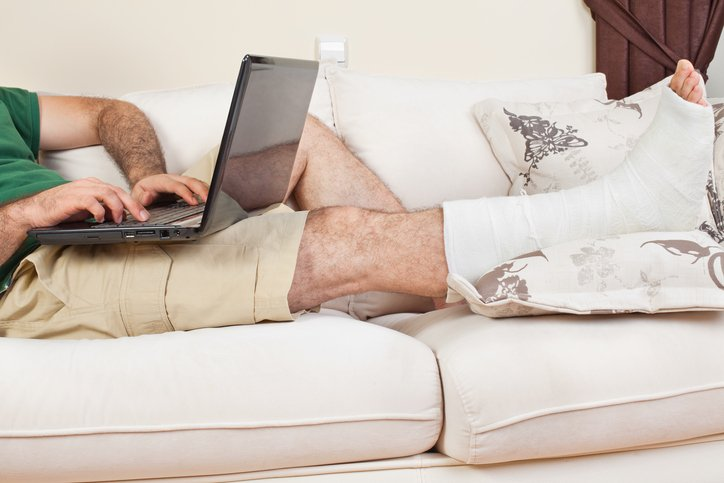 man on couch with laptop on lap and broken leg