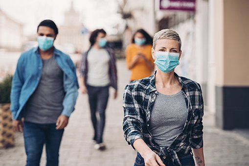 Four people wearing masks downtown