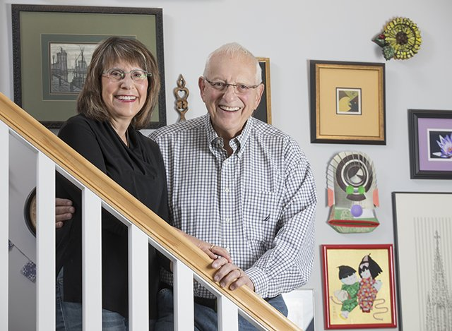 Bob and Ann Schulman in their home standing on stairs with photo wall behind