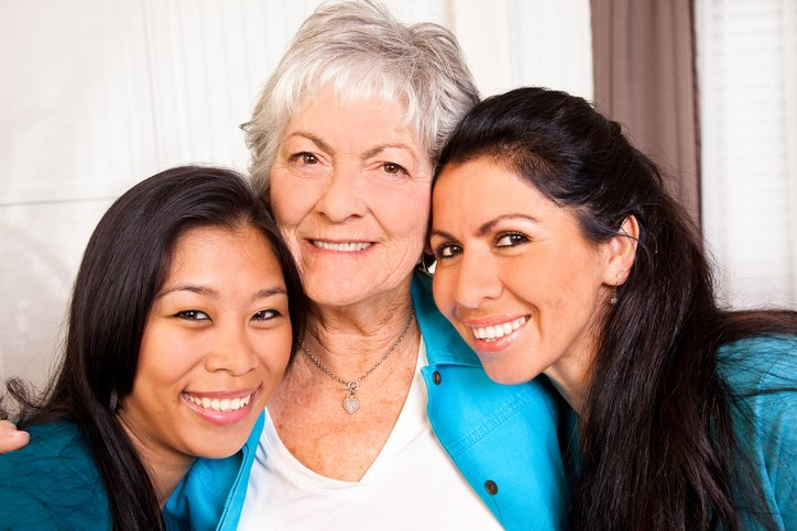 Photo of mother and two daughters close together smiling