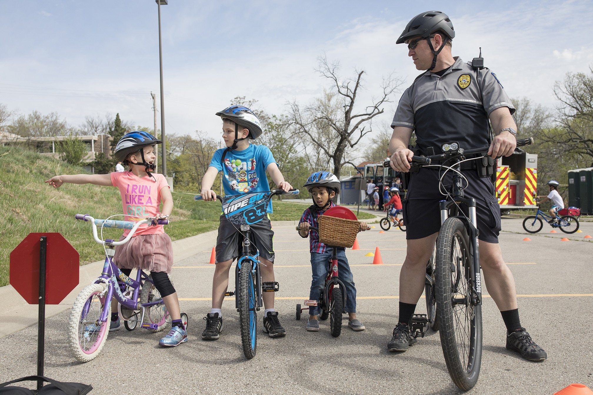 Three children and police officer on bicycles
