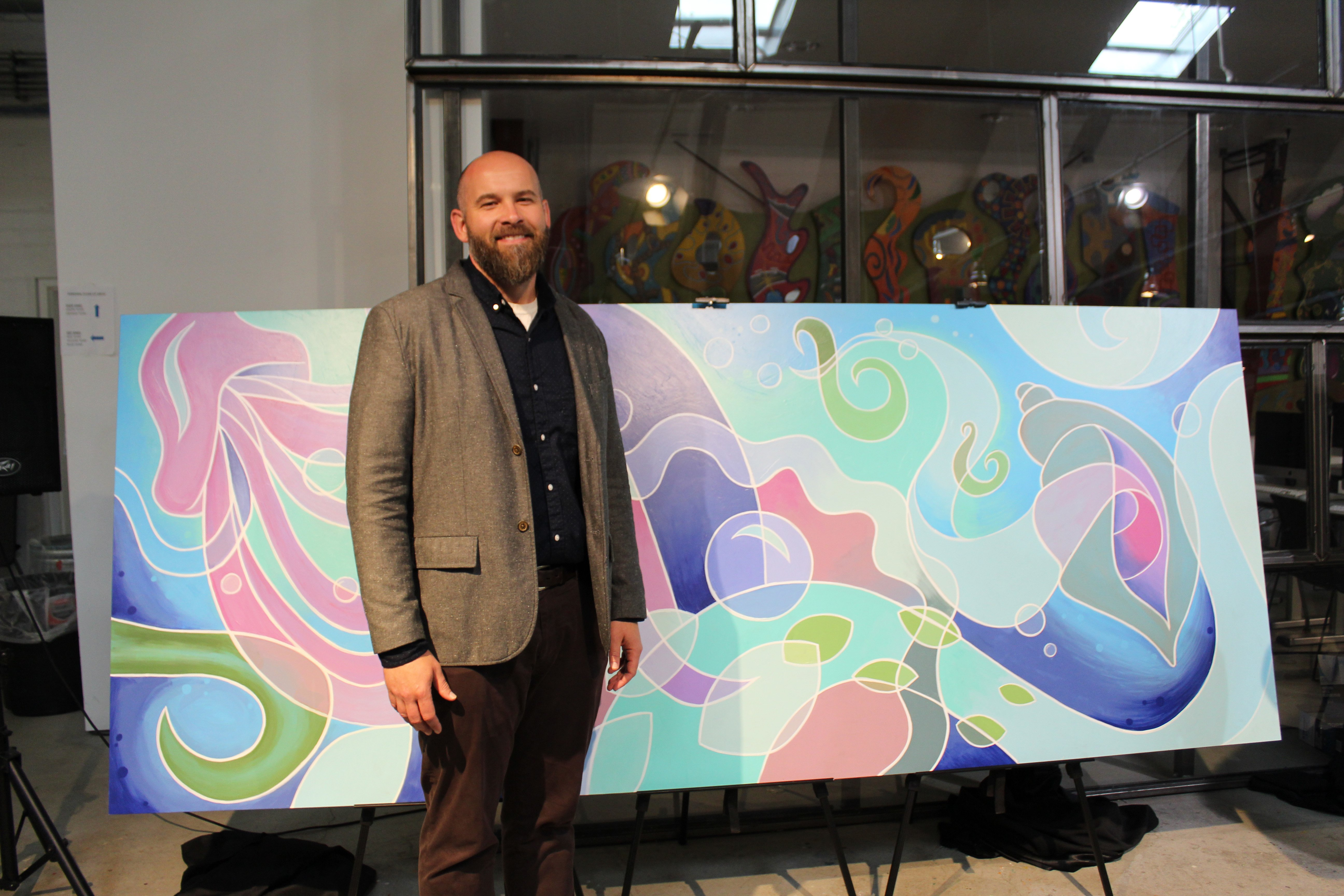 Derrick Hurst stands next to mural created by Van Go artists